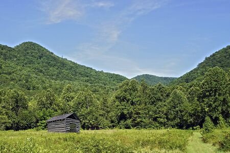 An old barn shed in a pasture surrounded by mountains.