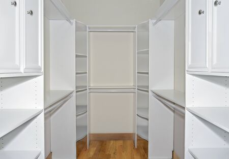 Interior of a closet with new shelves, racks and hangers for clothes, shoes and other personal items.