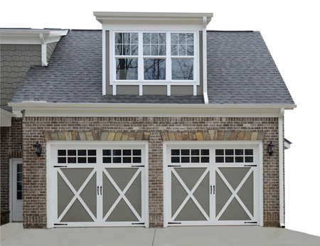 door: Double door garage at the entry of a new modern home.