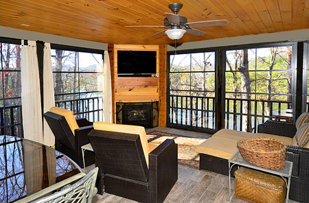 outdoor fireplace: An enclosed porch area on a house overlooking a lake.