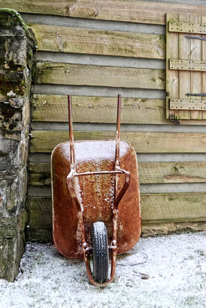 An old red wheelbarrow against the side of a log cabin in the winter.