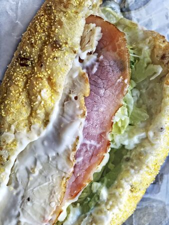 Close up of a sandwich with chicken, ham, lettuce, spinach and lots of mayonnaise.