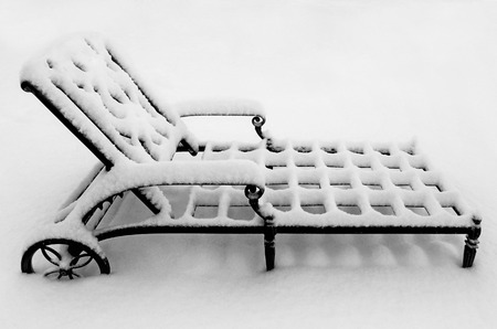 A metal lounge chair covered in snow, concept or metaphor for a harsh winter season.