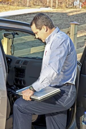 A business man putting his computer in the car getting ready to go to work.