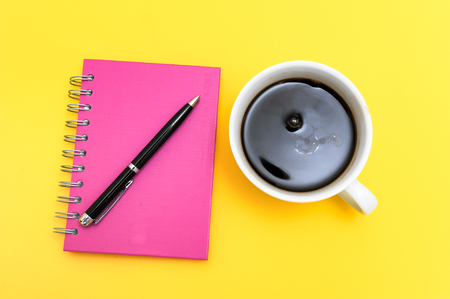 Black coffee in white cup with yellow background, and note book for notes.