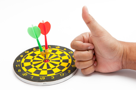 Hands holding thumbs and Dart board, with the concept To achieve the target Stock Photo