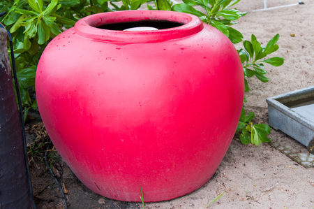 antique vase: Red water jar, to put water to use various benefits. Stock Photo