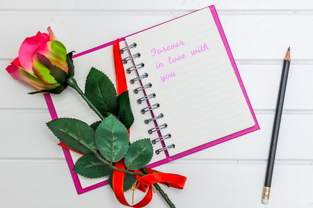 Note book that says Forever in love with you And there is a red rose.