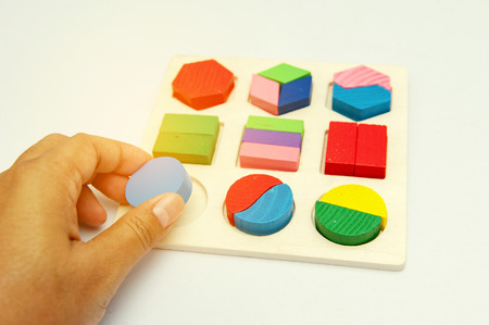 Hand playing puzzle toy,To practice childrens skills On a white background.