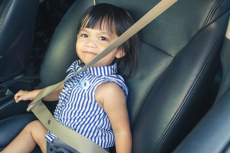 Little Asian girl in a car seat, wearing a safety belt for safety.