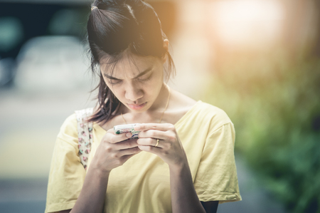 Asian girl playing phone serious.