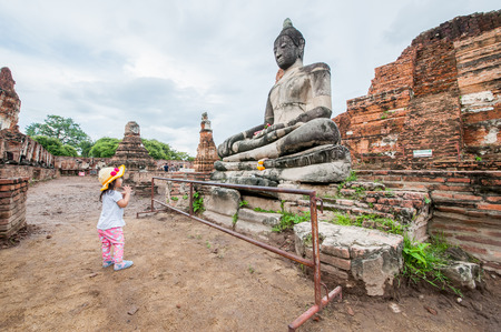 Ayutthaya Province, Thailand on August 27, 2017: Little girls are paying respect to the statue at the ancient temple is a popular tourist attraction of Ayutthaya, Thailand. Editorial