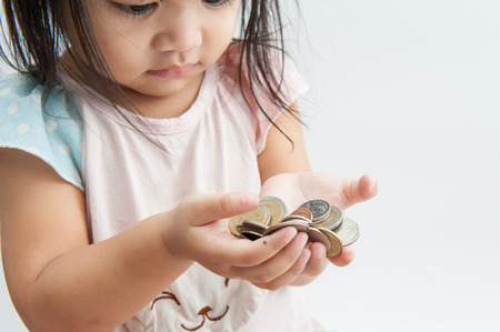 Little girls holding coins in hand.