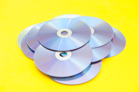 CDs, DVDs, on a yellow background. Stock Photo