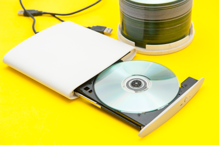 external dvd writer and cd,dvd On a yellow background. Stock Photo - 89091671
