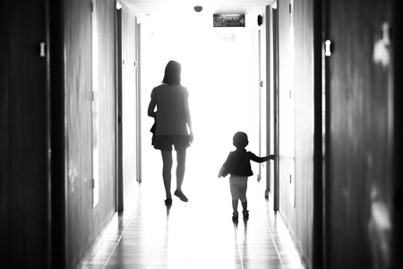 Black and white photo behind mother and daughter, walking away