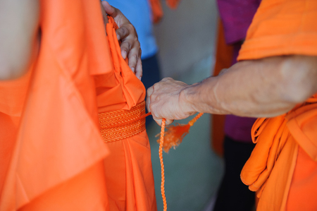 Perform the ordination and dress the monk.
