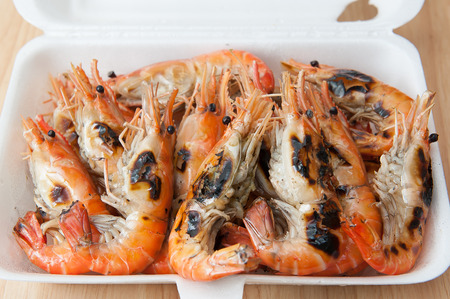 Grilled shrimp, fresh seafood, in foam box Фото со стока