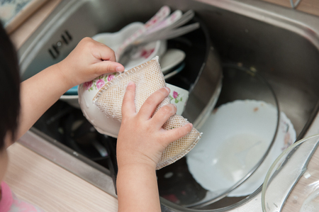 Little children are washing dishes. Stock fotó