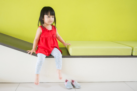 Asian little girl, sitting in a room, a child model taking pictures