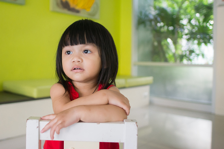 Asian little girl, sitting on a chair