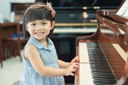 The cute little girl play piano With Grand Piano.