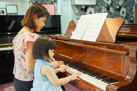 The cute little girl is learning piano with the teacher
