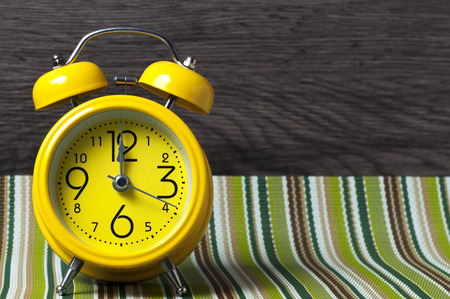 12 oclock: Yellow retro alarm clock on color mat shows 12 oclock