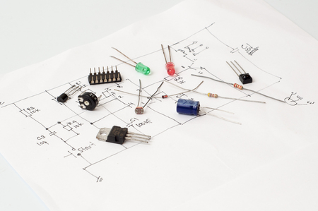 Electronics component on hand schematic drawing paper.