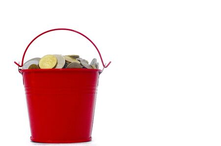 bucket of money: Coins and bucket over white background