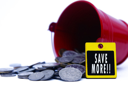 bucket spill out many coins and signboard shown SAVE MORE text shown over white background Stock Photo