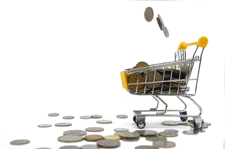 coins drops inside shopping cart over white background