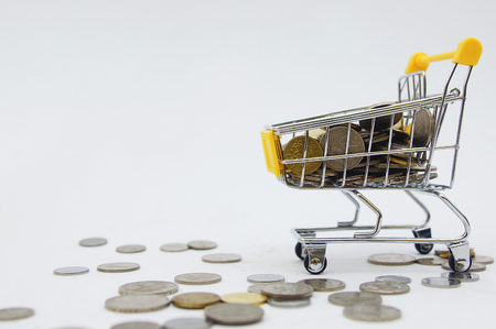 coins inside shopping cart over white background