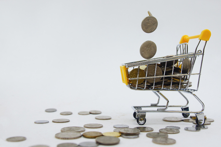 coins drops into shopping cart over white background
