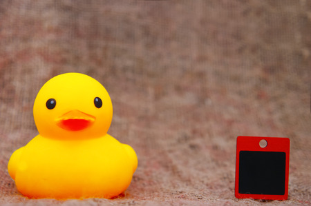 yellow duck toys and blank cardboard over sackcloth Stock Photo