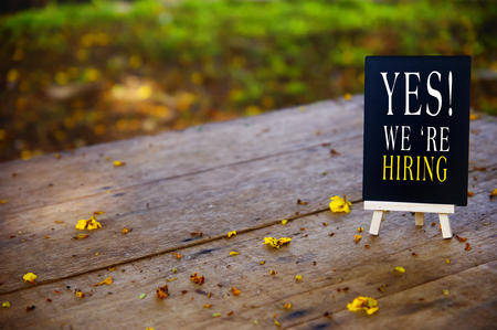 Job recruiting advertisement represented by WE ARE HIRING texts on the  blackboard over wooden table  with yellow