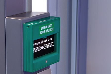 close up picture of a green emergency door release button Stock Photo