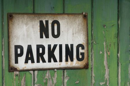 Close up of a no parking sign on a green wooden garage door Imagens