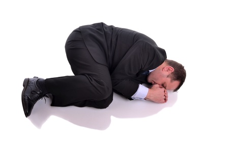 Businessman laying down in fetal position  Image is isolated on white