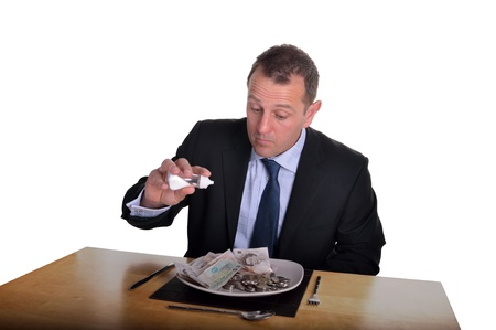 Image of a businessman with a plate full of money to eat Stock Photo