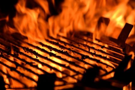 chorizos asados: Cerrar una imagen de una parrilla de barbacoa con llamas Foto de archivo