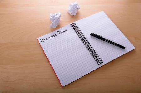 Image of an open book with pen on a desk. Starting to draft a new business plan