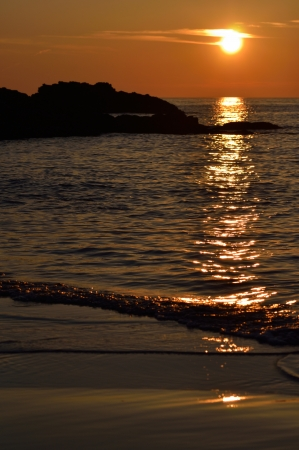 Image of a beach sunset with rocks silhouetted  Imagens