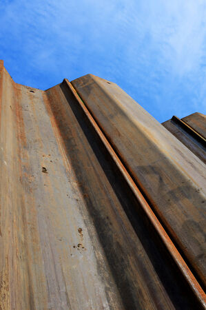 piling: Image looking up some earth supporting sheet piles from down in an excavation on a construction site