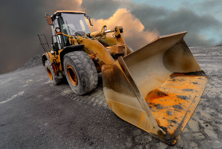 Image of a quarry Loader  excavator with a dramtic sky background Stock Photo