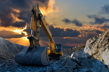 Image of a tracked excavator in a quarry with a setting sun and light rays photo