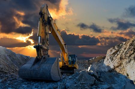 the equipment: Imagen de una excavadora a orugas en una cantera con una puesta de sol y los rayos de luz Foto de archivo