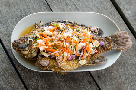 Deep fried red tilapia with herb and spicy sauce, Thai food photo