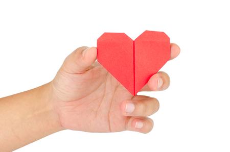 bondad: femenino corazón de papel explotación de la mano, aislado sobre fondo blanco.