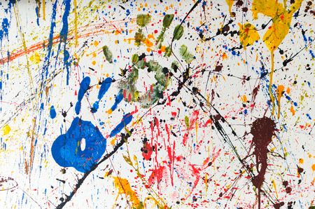 multiple stains: Multiple colorful children hand prints on white wall.